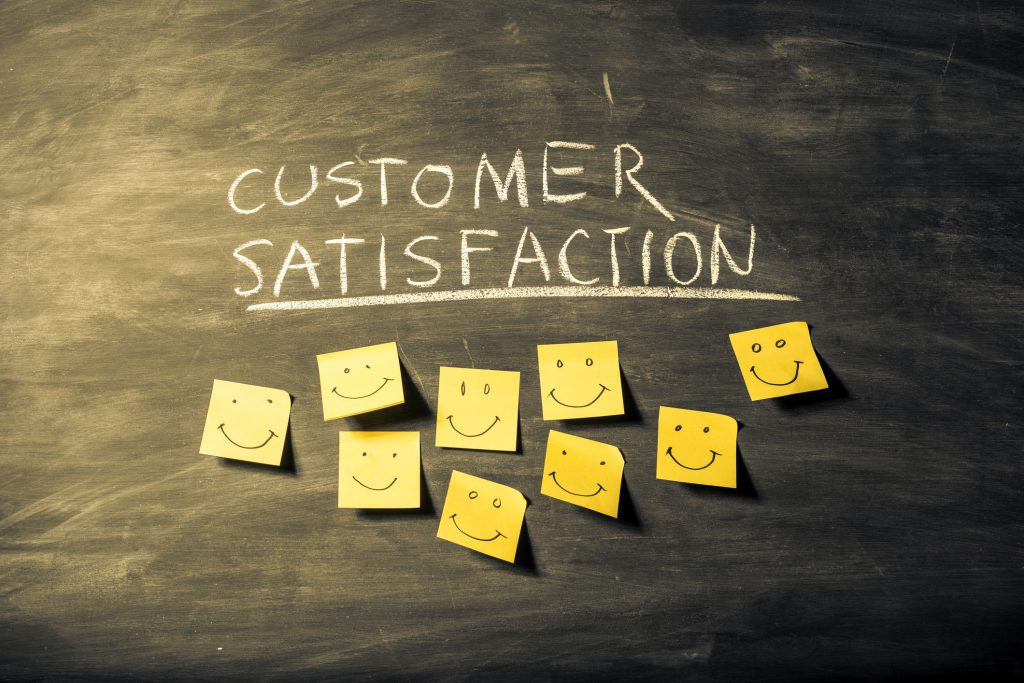 "Yellow sticky notes on black board below ""Customer satisfaction"" word. The notes have smiles drawn with a black color marker to represent the happy clients"