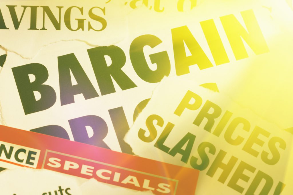 Newspaper headlines on bargains and money saving in golden light