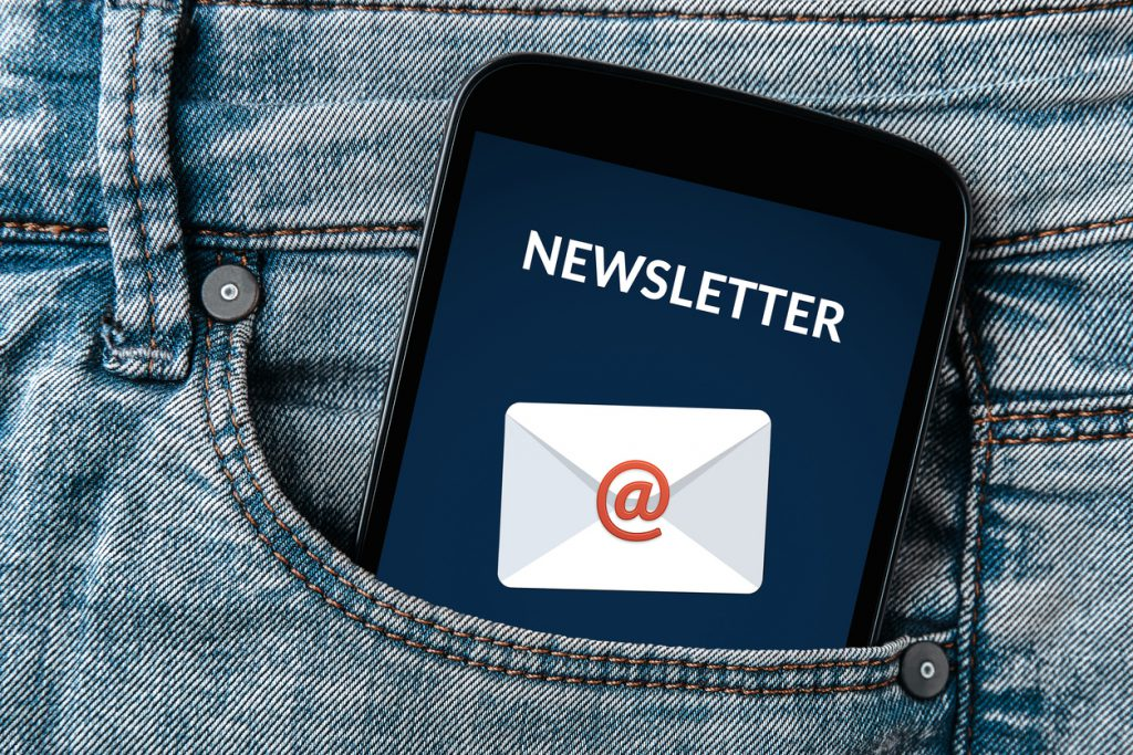 Subscribe newsletter concept on smartphone screen in jeans pocket