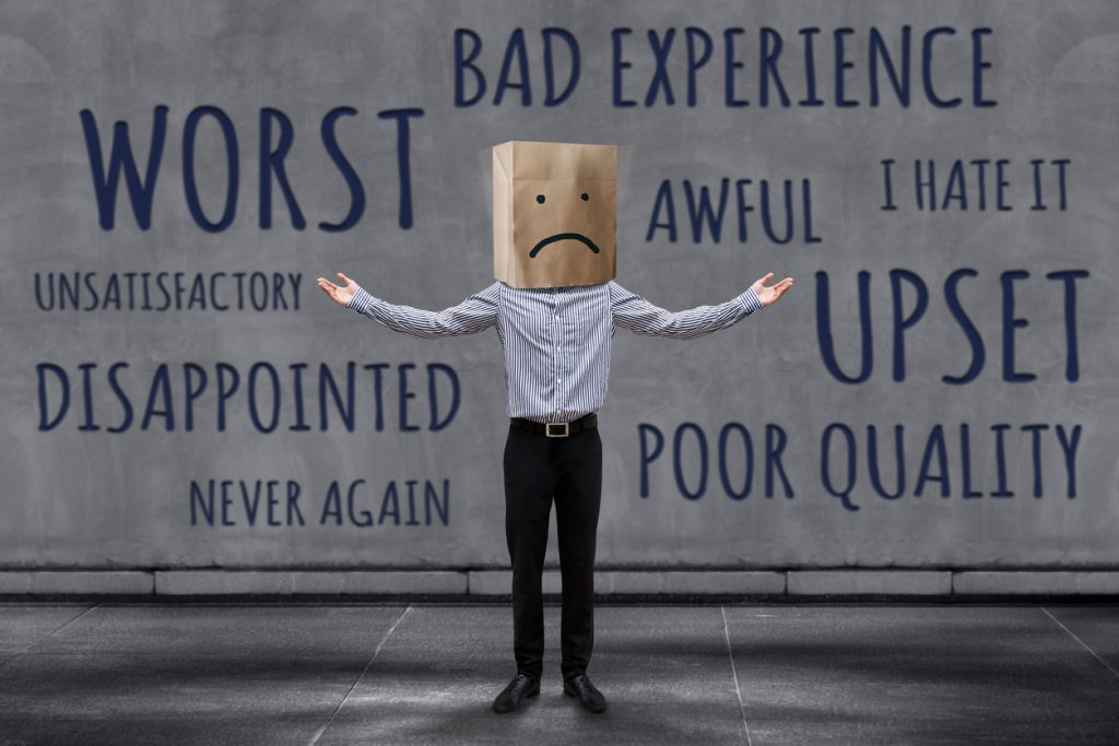 Customer Experience Concept, Unhappy Businessman Client with Sadness Emotion Face on Paper Bag, Blurred Concrete Wall with Wording of Negative Reviews as background